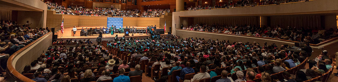 Graduates walk across the stage at the Meyerson Symphony Center.